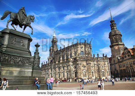 DRESDEN GERMANY - AUGUST 13 2016: Tourists walk on Theaterplatz and Majestic view on Saxony Dresden Castle and Katholische Hofkirche in Dresden State of Saxony Germany on August 13 2016.