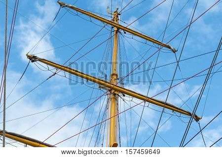Masts and rigging of a sailing ship against blue sky and clouds