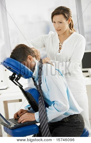 Businessman sitting on massage chair, getting back massage.?
