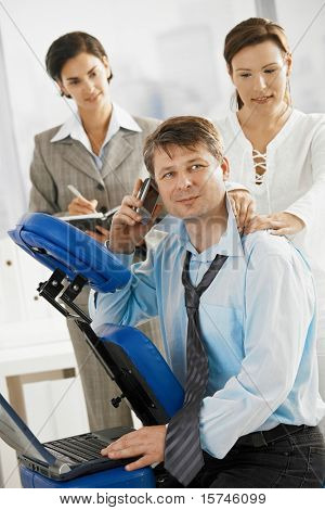 Occupied executive talking on mobile while getting neck massage in office. Secretary making notes the background.?