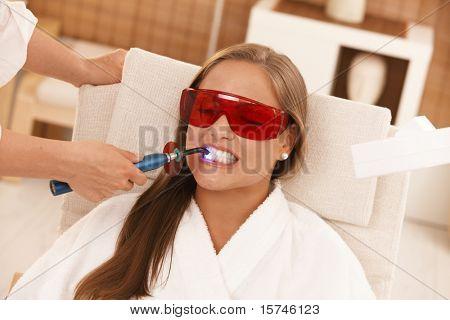 Jovem mulher recebendo tratamento no spa de clareamento laser.?
