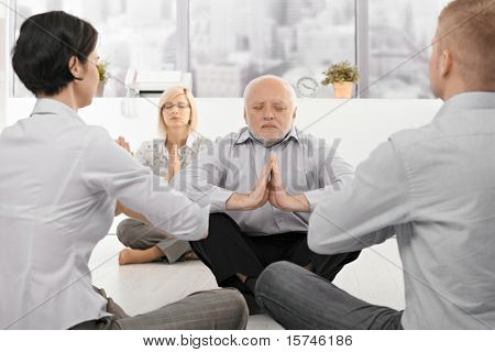 Businesspeople exercising yoga in office with eyes closed, focus on senior businessman.?