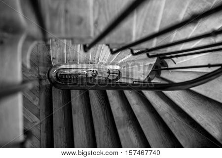 Black-white photo of wooden spiral staircase in old building Paris France.