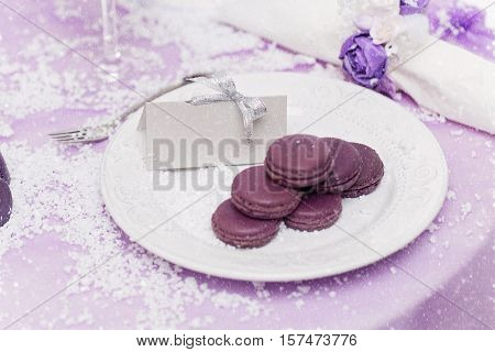 Dessert plate with purple macarons served on wedding table. Empty guest card with copy space.