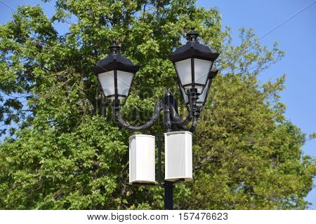 The Loudspeaker On The Pole. Outdoor Speakers For Fun Walking In The Park. A Pillar With Lights And