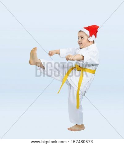 Boy in karategi beats kicking on the light background