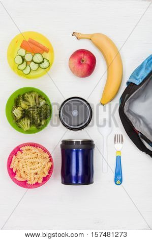 Top view on lunch box thermos and healthy food options for school. Snacks for the day. Hot lunch take away. Cucumbers carrots broccoli apple banana and pasta.