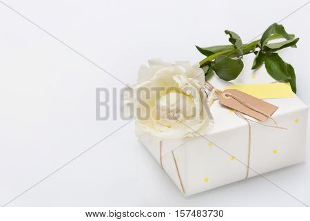 Nice present packed in white paper with small yellow stars with beautiful peony flower on white wooden background. Wrapped gift for birthday party. Mock-up. Holidays concept.