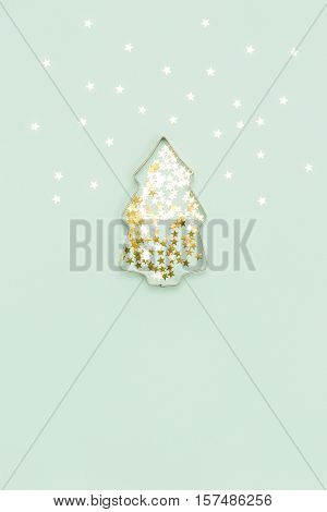 Christmas tree made with mold for the cookies and silver sparkling stars on blue background. Flat lay. Holidays and winter concept