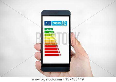 Man holding smartphone with energy efficiency chart. Savings in home concept