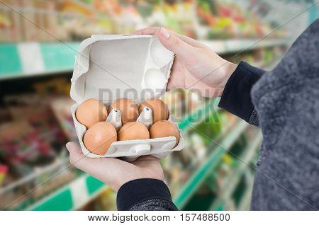 Man Holding Egg Box In Supermarket