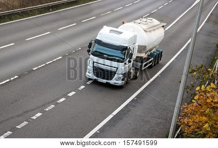 White cistern truck in motion on the road