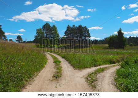 Rural scenic landscape with crossroad on hill in forest. Two different directions. Concept of choose the correct way. Right and left path. Junction fork split road. Beautiful summer scenery.