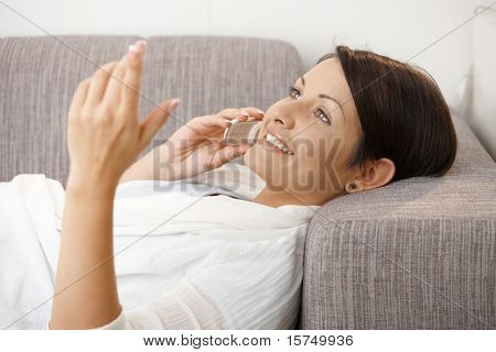 Profile portrait of happy woman talking on mobile, lying on sofa at home.?