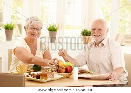 Happy elderly couple having breakfast in kitchen, smiling at camera.?