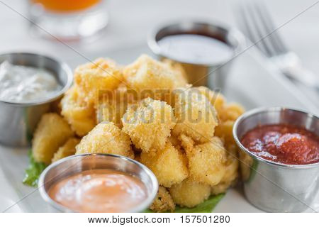 A plated dish of fried chees curds and dipping sauces