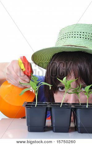 Young Woman Spraying Water Onto Plants Isolated