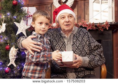 Adorable Little Boy Gives A Christmas Gift To His Grandfather