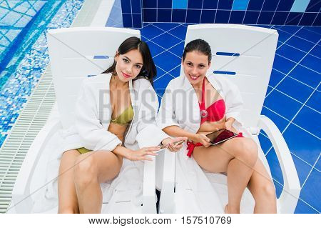 Young girls friends messaging with friend on her smartphone. Relaxation spa and technology social networks concept