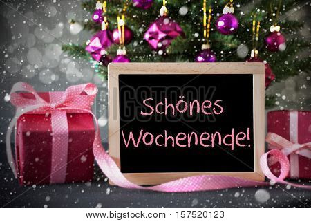 Chalkboard With German Text Schoenes Wochenende Means Happy Weekend. Christmas Tree With Rose Quartz Balls, Snowflakes And Bokeh Effect. Gifts Or Presents In The Front Of Cement Background.