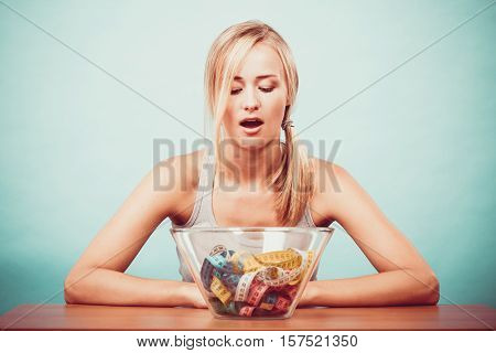 Diet healthy eating weight loss and slim body concept. Fit fitness girl and bowl with many colorful measuring tapes young woman bored of dieting
