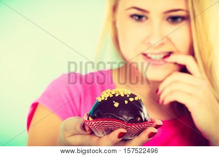 Diet sweets food concept. Cute blonde attractive woman thinking about eating delicious chocolate cupcake