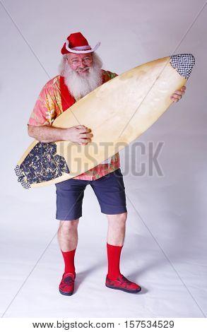 Surfing Santa. Rocker Santa. Causal Santa. Santa Claus Rocks Out with his surfboard as he plays it like an Air Guitar.