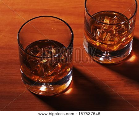 Highball whiskey glass with ice on wooden background. Close up.