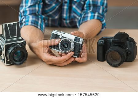 Unrecognizable man shows simple film camera. Different generation of camera comparison. Technology progress, hobby, profession concept