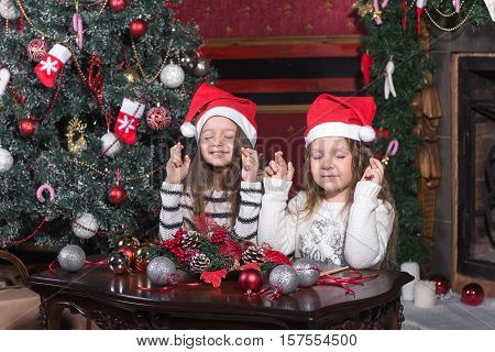 Little beatuful girls makes a wish at Christmas near tree at home