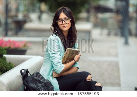 Confident asian student girl city portrait. Woman sitting on bench outside with book in casual business suite. Beautiful young mixed race Asian Caucasian woman.