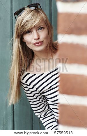 Beautiful woman peering out from brick wall portrait