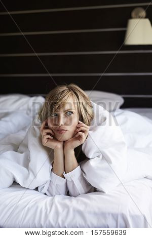 Beautiful woman deciding whether to get out of bed