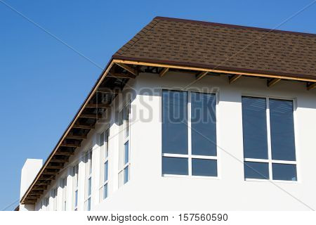 unfinished construction on the roof of a house with white walls and large windows