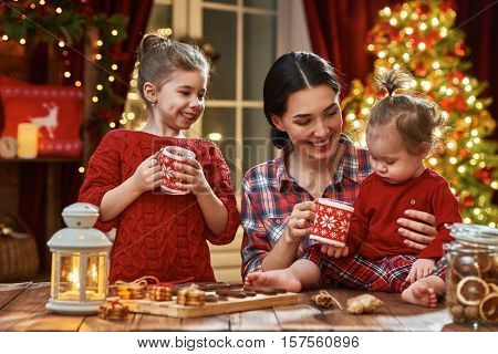 Merry Christmas and Happy Holidays. Time of family tea party. Mother and her children daughters are drinking warm tea with Christmas cookies.