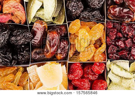 Assortment of dried fruits closeup background in square cells. Decorative pattern of dry exotic fruit. Top view.