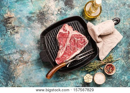 Raw T-bone Steak on frying grill pan with meat fork, oil and seasoning on blue concrete background, top view