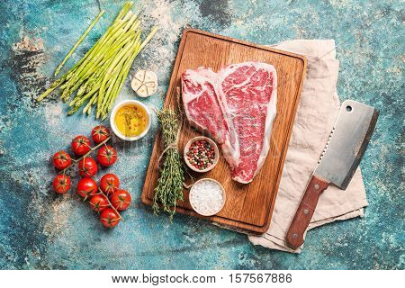 Raw T-bone Steak for grill or BBQ on cutting board over blue concrete background, top view