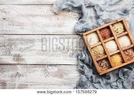 Varieties of rice in printers box, jasmine wild white pearl forbidden jade basmati and barley. Top view