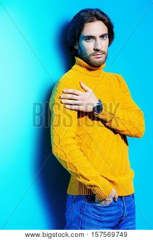 Handsome man wearing yellow pullover. Men's beauty, fashion. Hairstyle for men. Blue background.