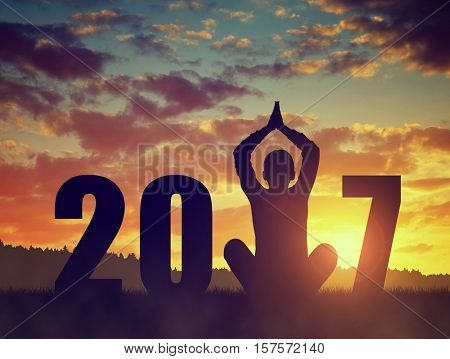 Silhouette of a girl practicing yoga in the New Year 2017
