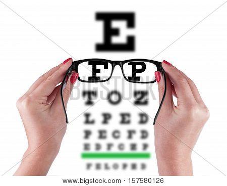 Black Eye Glasses in women's hand Isolated on eyesight test chart background
