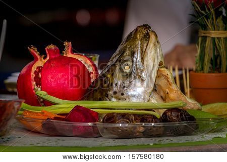 Rosh Hashanah, traditional dish with the fish head, pomegranate, fruits and vegetables for Jewish New Year