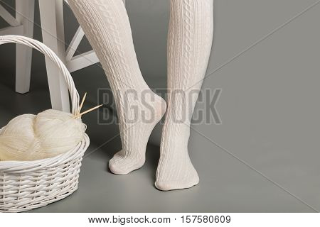 Female feet in white knitted tights near the basket with yarn and knitting.