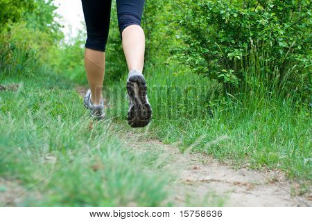 Woman Cross Country Running On Trail