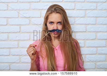 Mid shot portrait of active and positive young woman. Funny frowning young attractive woman holding paper moustache over white brick background