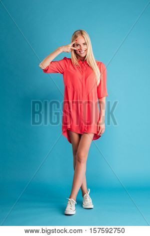 Full length portrait of a smiling blonde woman in red dress standing and showing victory sign isolated on a blue background
