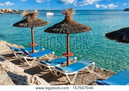 Beautiful seascape with yacht and sun umbrellas. Spain Majorca