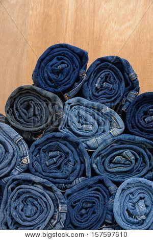 Stack of Lot of different blue jeans on wooden background