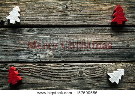 Wooden carved christmas tree on wooden background. Idea for tinker or hobby creative.